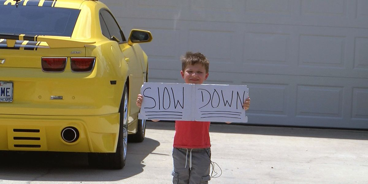 5-year-old boy using own signs and thumbs up to stop speeders in his neighborhood