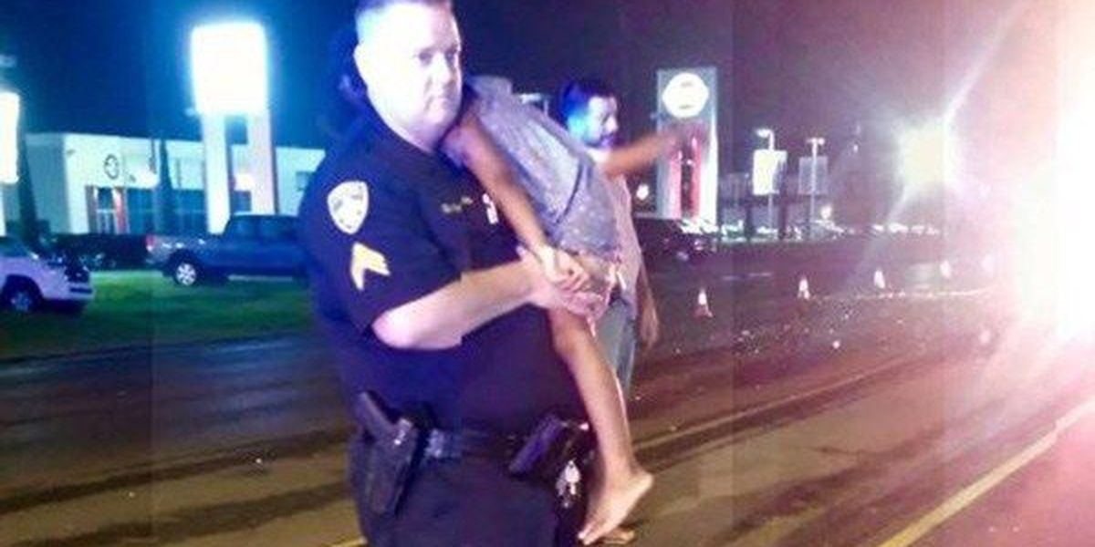 Police officer cares for and comforts little girl after crash